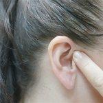 Девушка пальцем прикрывает ухо