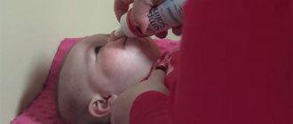 Мама капает нос ребенку