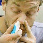 мужчина брызгает в нос